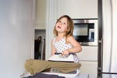 Menina que passa e que canta na cozinha Imagens de Stock