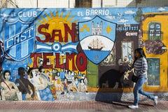 Menina que passa na frente de uma pintura mural na vizinhança de San Telmo, Buenos Aires, Argentina Imagens de Stock