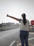 Menina que pede um passeio na borda da estrada de uma estrada Imagem de Stock Royalty Free