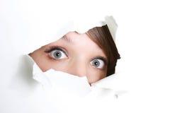 Menina que peeping através do furo no papel imagens de stock royalty free