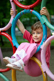 Menina que pendura em anéis um campo de jogos das crianças Imagens de Stock