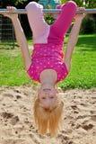 Menina que pendura upside-down foto de stock