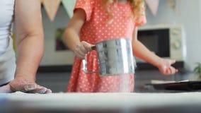 Menina que peneira a farinha na cozinha vídeos de arquivo