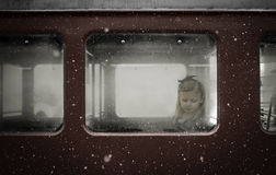 Menina que pensa em uma janela de carro vermelha do trem com queda da neve do inverno Imagens de Stock