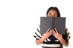 Menina que pensa sobre seu livro. Imagens de Stock Royalty Free