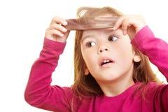 Menina que penteia seu cabelo Fotografia de Stock Royalty Free