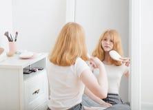 Menina que penteia seu cabelo na frente do espelho fotografia de stock