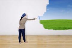 Menina que pinta o campo verde na parede Foto de Stock Royalty Free