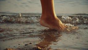 Menina que pisa na areia molhada da linha costeira Os pés da jovem mulher que vão ao longo do oceano encalham durante o por do so filme