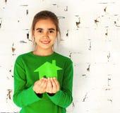 Menina que prende a casa verde nas mãos Fotografia de Stock