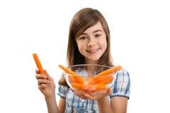 Menina que prende cenouras frescas Fotos de Stock Royalty Free
