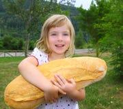 Menina que prende a criança com fome do tamanho grande do humor do pão imagens de stock