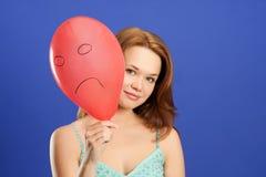 Menina que prende o balão irritado vermelho Fotografia de Stock Royalty Free