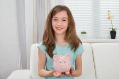 Menina que prende o banco Piggy Imagem de Stock Royalty Free