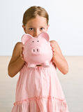 Menina que prende o banco piggy Fotos de Stock