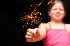 Menina que prende o fogo-de-artifício amarelo do sparkler com mão Fotografia de Stock Royalty Free
