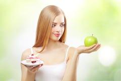 Menina que prende um bolo e uma maçã fotos de stock