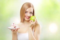 Menina que prende um bolo e uma maçã imagem de stock royalty free
