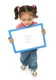 Menina que prende um sinal em branco Fotografia de Stock