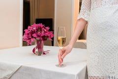 Menina que prende um vidro do champanhe O ramalhete do casamento no fundo fotos de stock royalty free