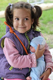Menina que prende uma boneca Fotografia de Stock