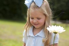 Menina que prende uma flor Imagem de Stock Royalty Free