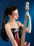 Menina que prende uma guitarra baixa Fotografia de Stock