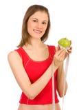 Menina que prende uma maçã e uma fita da medida Imagem de Stock