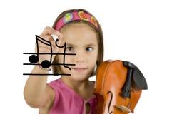 Menina que prende uma pena e um violino fotografia de stock royalty free