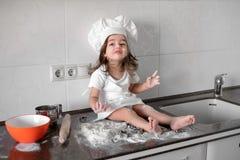 Menina que prepara cookies na cozinha em casa foto de stock