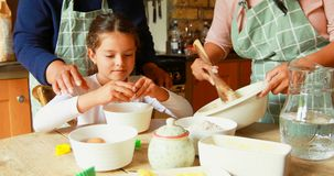 Menina que prepara o alimento com a família na cozinha 4k filme