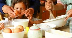 Menina que prepara o alimento com a família na cozinha 4k video estoque