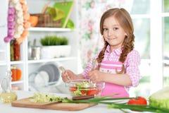 Menina que prepara a salada vegetal Imagem de Stock