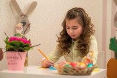 Menina que prepara-se para a Páscoa - pintura, desenho colorido na sala Foto de Stock Royalty Free