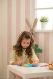 Menina que prepara-se para a Páscoa - pintura, desenho colorido na sala Fotos de Stock Royalty Free