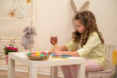 Menina que prepara-se para a Páscoa - pintura, desenho colorido na sala Fotografia de Stock Royalty Free