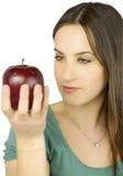 Menina que presta atenção à maçã vermelha grande Fotografia de Stock Royalty Free