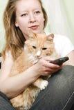 Menina que presta atenção à tevê com gato Imagens de Stock Royalty Free
