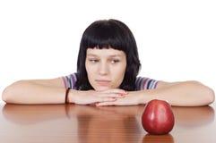 Menina que presta atenção a uma maçã vermelha Fotografia de Stock