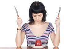 Menina que presta atenção a uma maçã vermelha Foto de Stock
