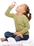 Menina que pulveriza seu nariz Imagens de Stock