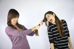 Menina que puxa o cabelo de seu amigo Fotos de Stock Royalty Free