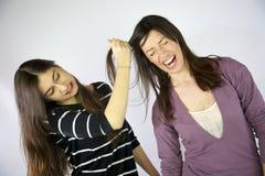 Menina que puxa o cabelo longo duro de seu amigo Imagem de Stock