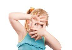 menina que quadro sua face com suas mãos Imagens de Stock