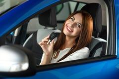 Menina que realiza em chaves das mãos do carro novo foto de stock