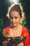 Menina que realiza nas mãos os cogumelos grandes imagem de stock