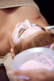 Menina que recebe a máscara facial cor-de-rosa cosmética fotografia de stock royalty free