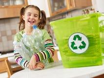 Menina que recicl frascos plásticos Foto de Stock Royalty Free
