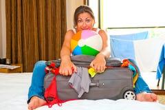Menina que recolhe o mar das malas de viagem Fotografia de Stock Royalty Free