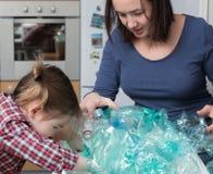 Menina que recolhe o plástico com sua mãe Imagens de Stock Royalty Free